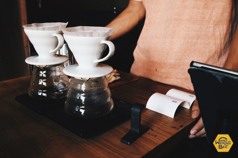 Barista making two pour-over coffees while handling other customers (multitasking)