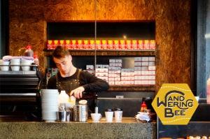 コーヒーマシンの裏でコーヒーを淹れるバリスタ